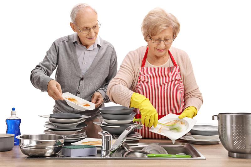 Elderly couple doing the dishes together royalty free stock photography