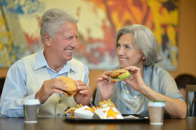 Elderly couple eating fast food. Portrait of beautiful elderly couple eating fast food royalty free stock image