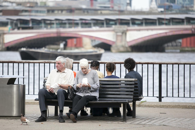 An elderly couple eating popcorn, sitting on a bench overlooking the Thames. South Shore of the Thames royalty free stock photo