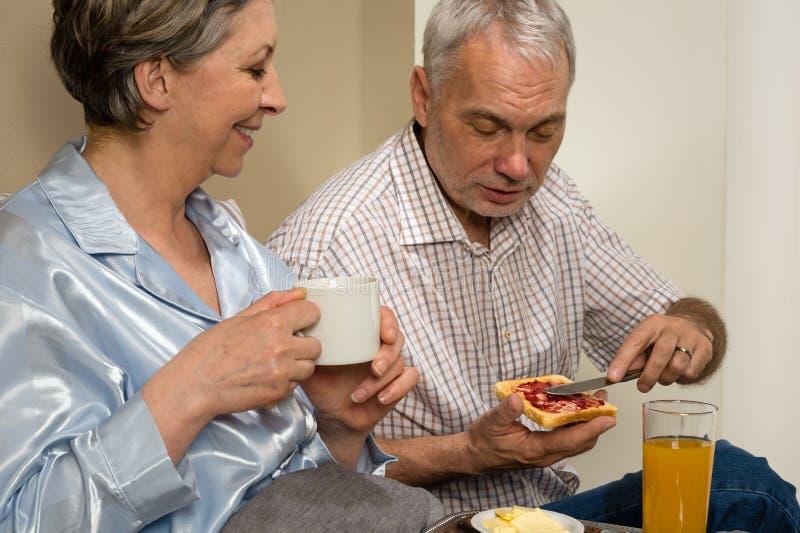Elderly couple eating romantic breakfast in bed. Elderly couple eating romantic breakfast together in bed stock photos