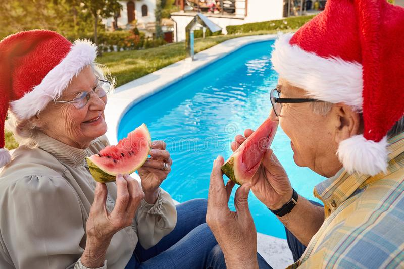 Elderly couple enjoying in watermelon and celebrating  Christmas time. Happy elderly couple enjoying in watermelon and celebrating  Christmas time royalty free stock photo