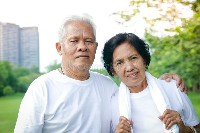 Elderly couple exercising in the garden royalty free stock photo