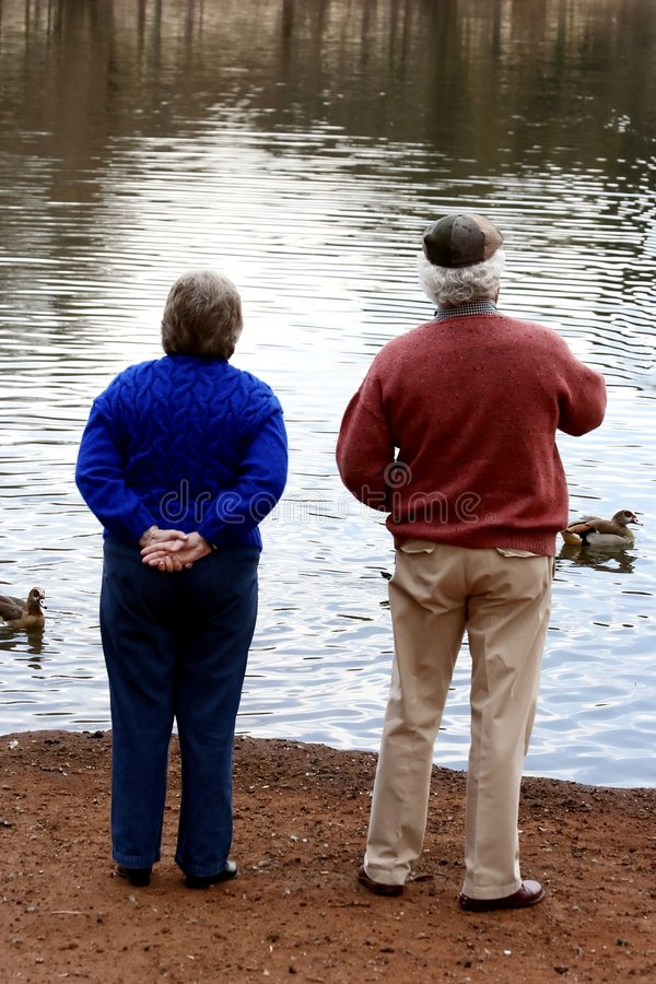 Elderly Couple Feeding Ducks royalty free stock images