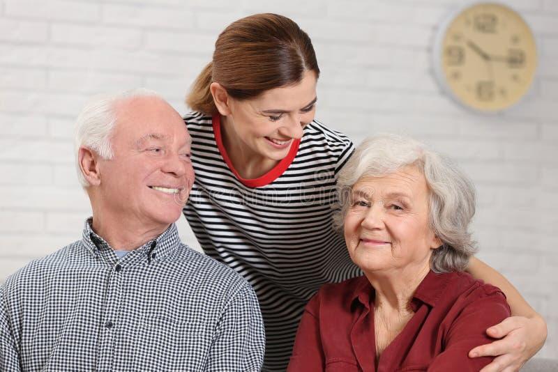 Elderly couple with female caregiver stock photography