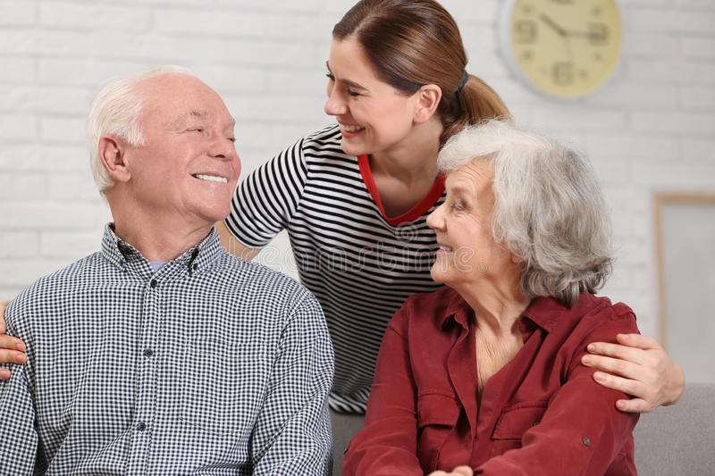 Elderly couple with female caregiver stock images