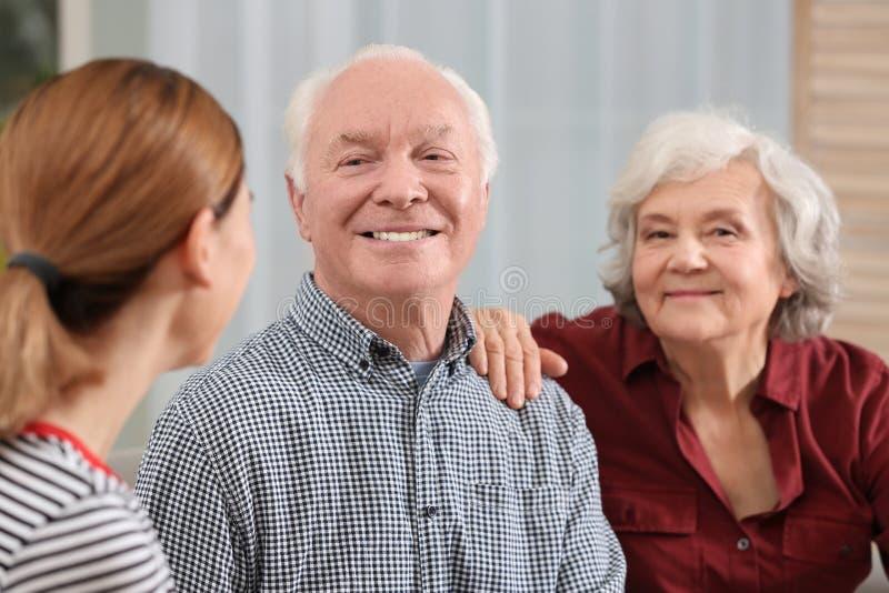 Elderly couple with female caregiver royalty free stock photo