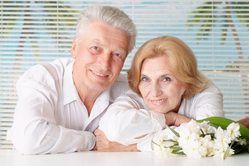 Elderly couple with flowers. Resting at home royalty free stock photos