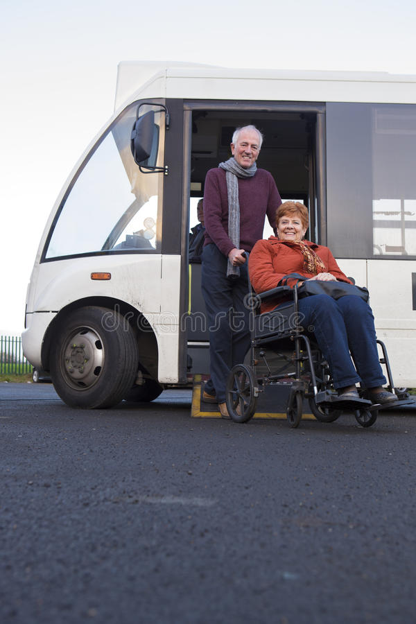 Elderly couple getting off their community bus stock photography