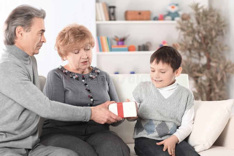 Elderly couple gives a gift to their grandson on his birthday stock images