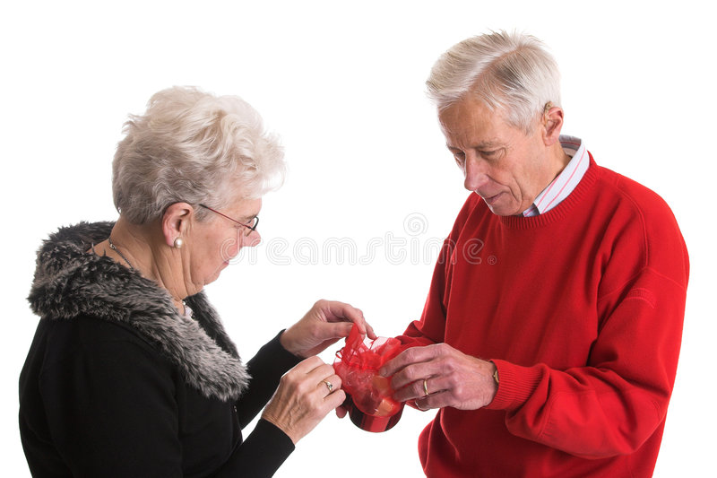 Elderly couple giving presents royalty free stock photography