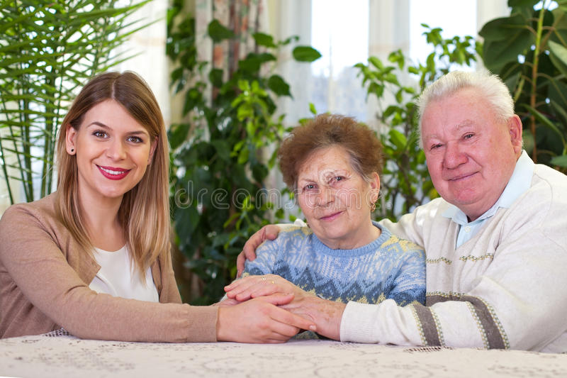 Elderly couple with happy caregiver royalty free stock photo