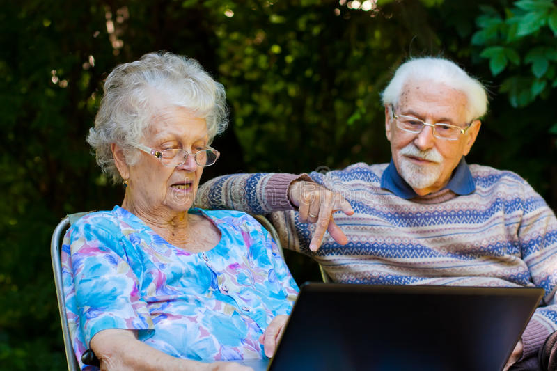 Elderly couple having fun with the laptop outdoors. An elderly couple having fun with the laptop in the garden, outside stock images