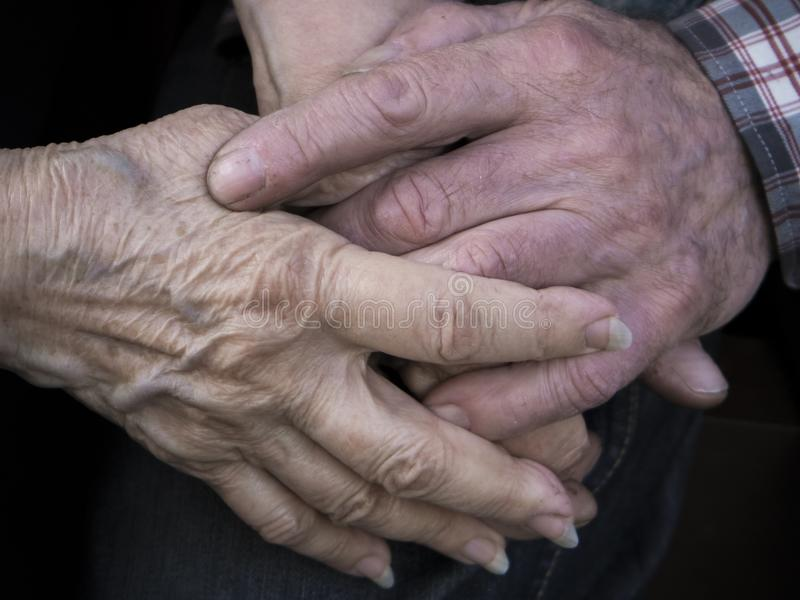 Elderly couple holding hands, expression of love and tenderness stock photo