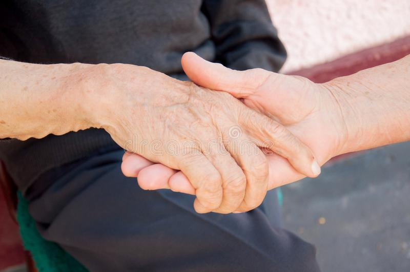 Elderly couple holding hands. Love. Older people hold each other`s hands. Elderly couple holding hands. Old people need each other.Older people hold each other` royalty free stock images