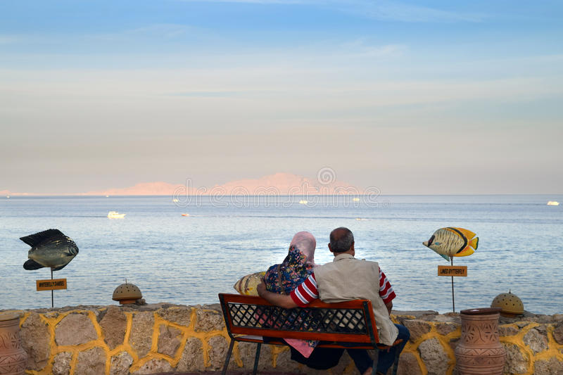 Elderly couple hugging and looking at the sea. Elderly couple hugging, sitting on a bench and looking at the sea stock image