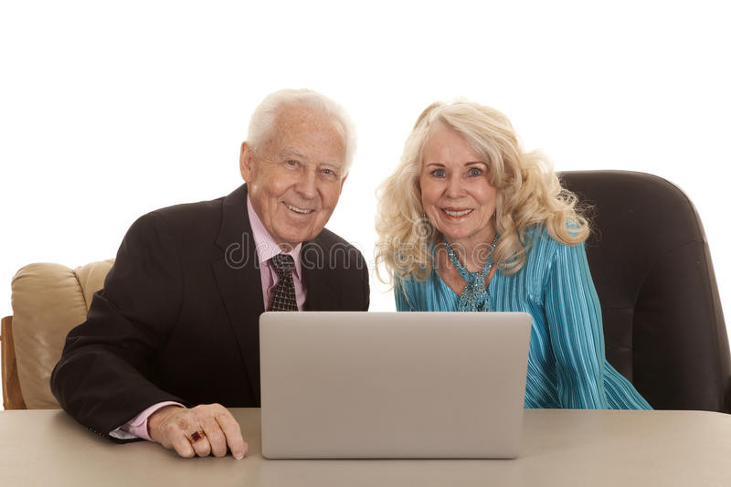 Elderly couple laptop both looking smiling. An older couple business people working together on a laptop stock images