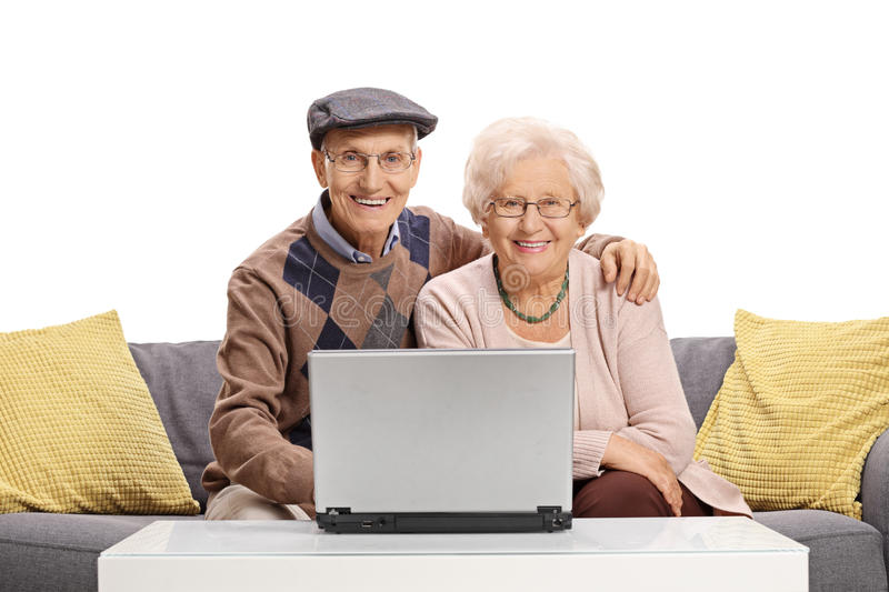 Elderly couple with a laptop sitting on a sofa stock photo