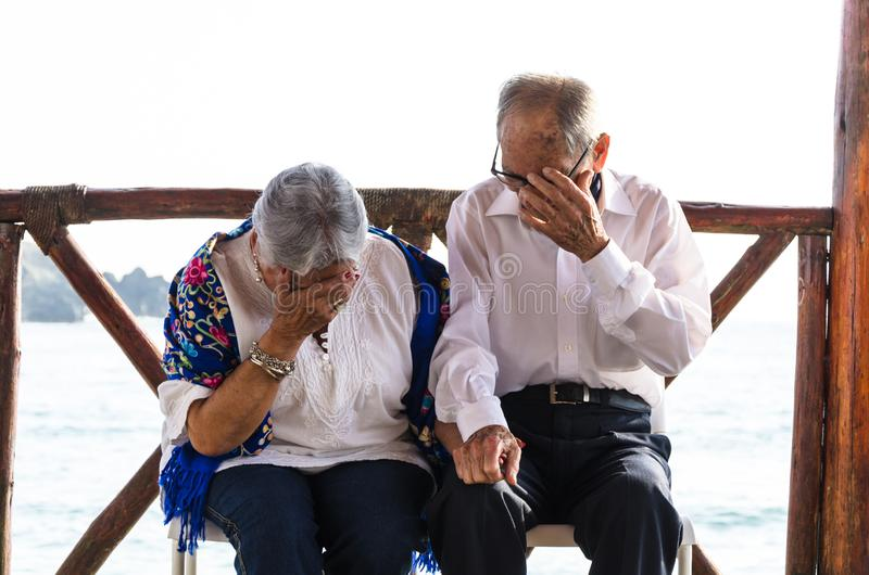Elderly couple looking at each other laughing. Elderly couple with the sea background stock photography