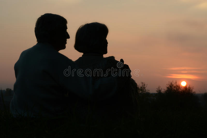 Elderly couple looking at sunset royalty free stock images