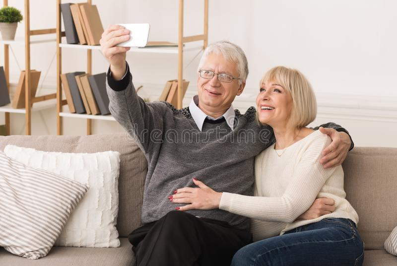 Elderly couple making video call from smartphone royalty free stock photo