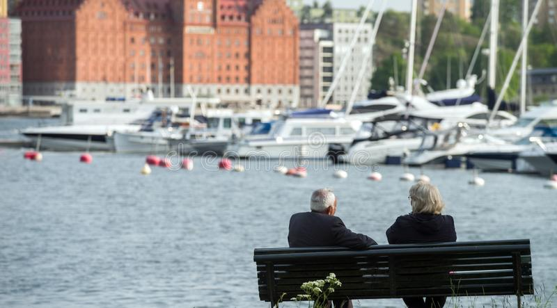 An elderly couple, a man and a woman with gray hair, sit on a bench by the lake on the background of yachts and modern houses. stock image