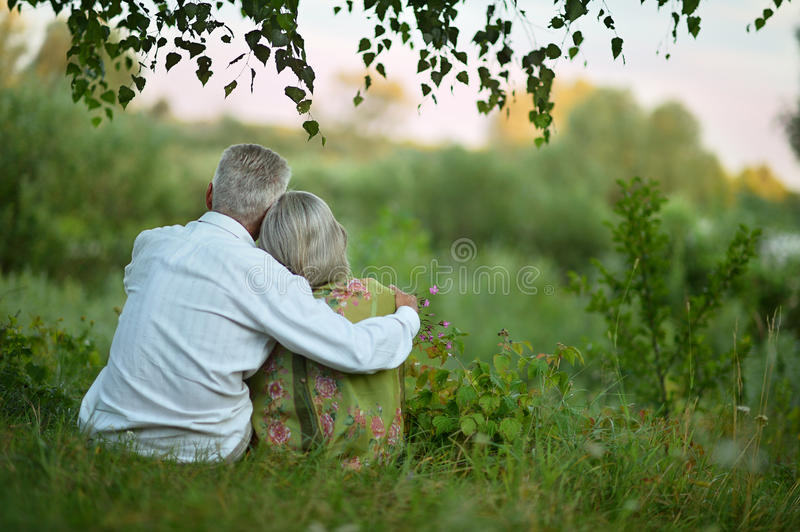 Elderly couple on nature at summer royalty free stock photo