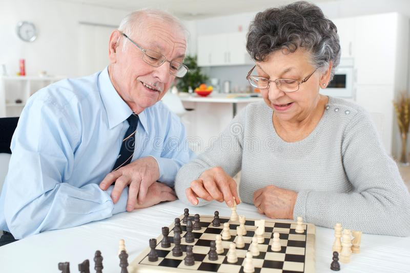 Elderly couple playing chess. Couple stock photography