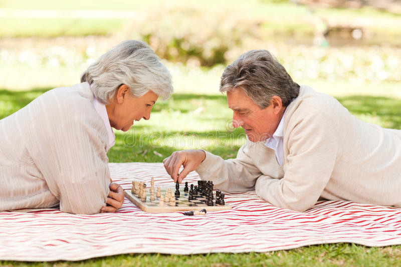 Elderly couple playing chess. On a slick royalty free stock image