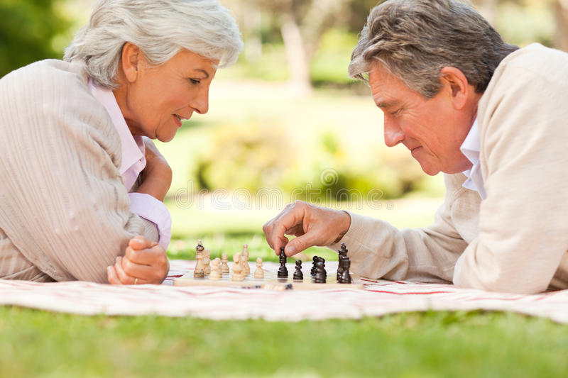 Elderly couple playing chess. On the grass royalty free stock photo