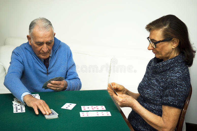 Elderly couple playing a game of cards stock images