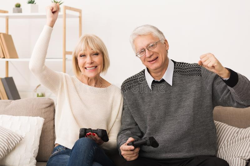 Elderly couple playing video games, celebrating victory stock photography