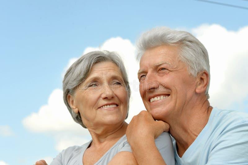 Elderly couple posing against the sky. Happy elderly couple posing against the sky royalty free stock photo