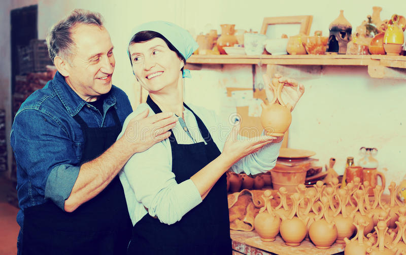 Elderly couple at pottery workshop. Elderly couple among the pottery at the workshop stock image