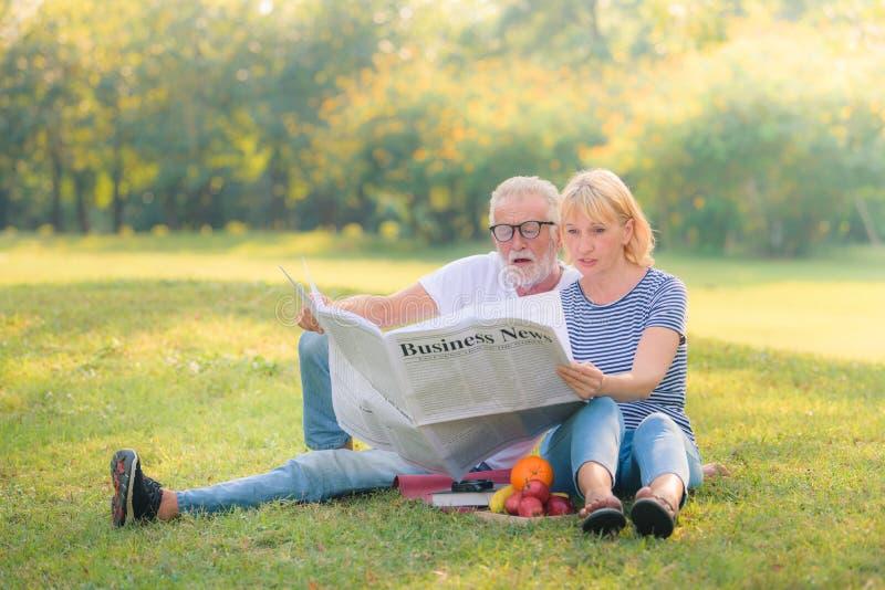 Elderly couple reading newspaper in garden at sunset. Concept couple elder love stock photo