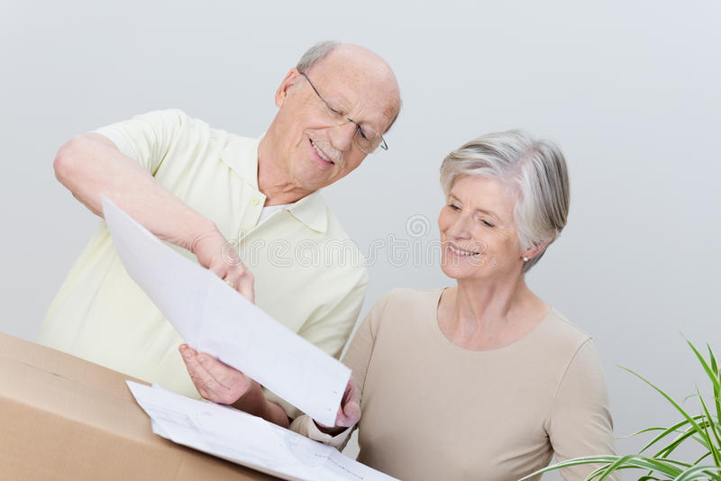 Elderly couple reading a plan as they move house royalty free stock photos