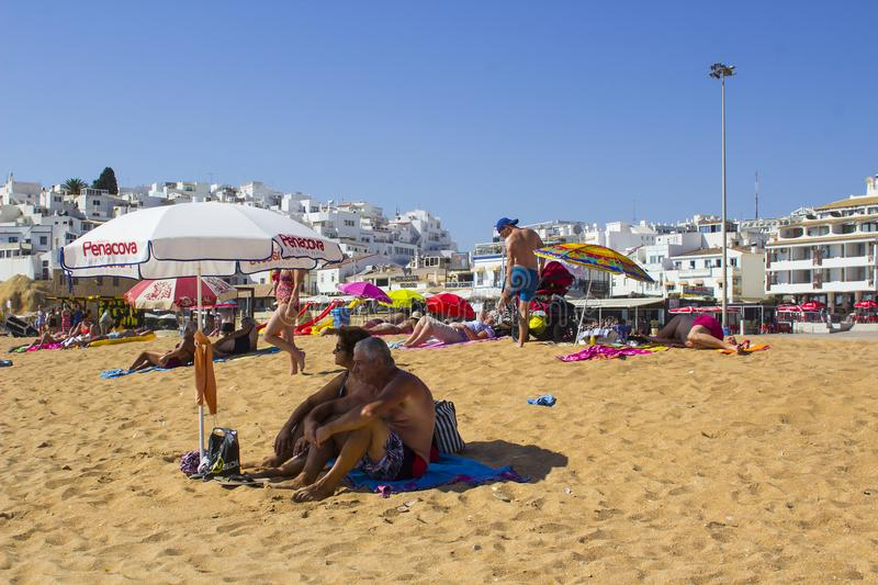 An elderly couple relaxing in the shade of a sun brolly on the sandy beach in Albuferia in Portugal royalty free stock photography