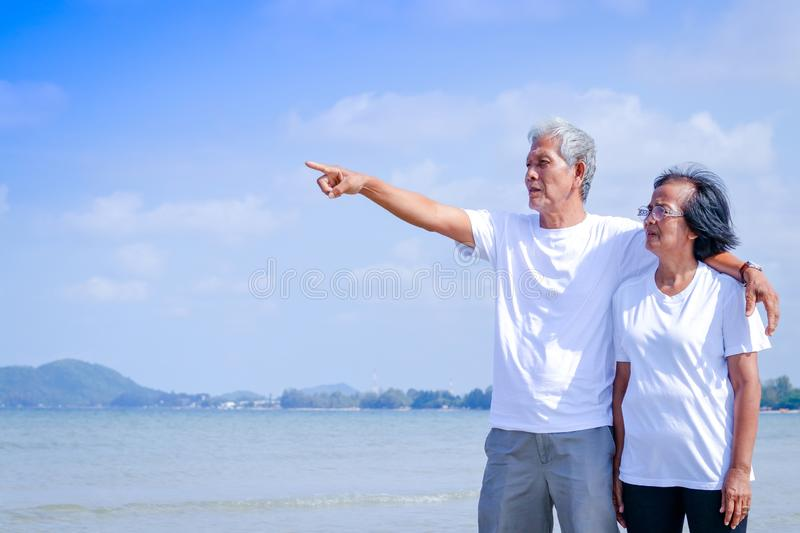 An elderly couple resting at the sea. An elderly Asian couple wears a white shirt. They walked to the beach. He stood hugging each other and pointing his finger stock image