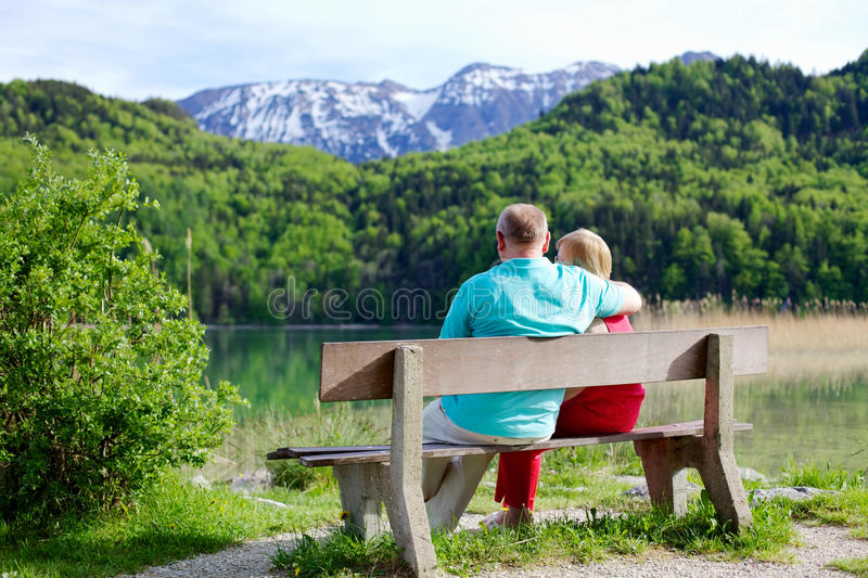 Elderly couple rests on bench royalty free stock photos
