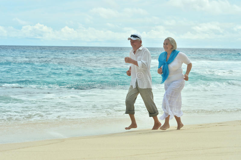 Elderly couple running on beach. Portrait of a happy elderly couple running on beach royalty free stock images