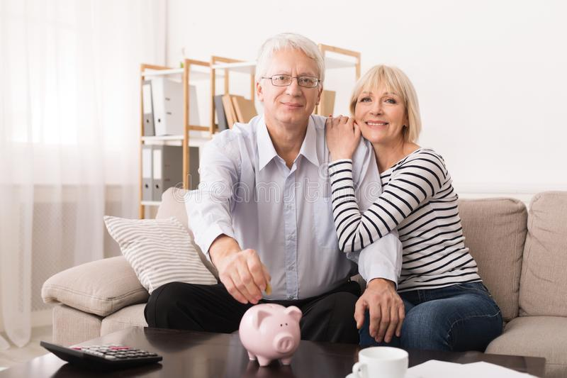 Elderly couple saving money in piggybank at home stock image