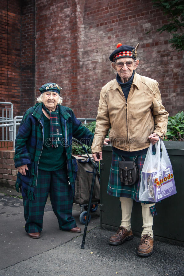 Elderly couple in Scottish dress on the street. A senior man and woman in traditional Scottish dress pause for a breath on the street in front of a brick wall