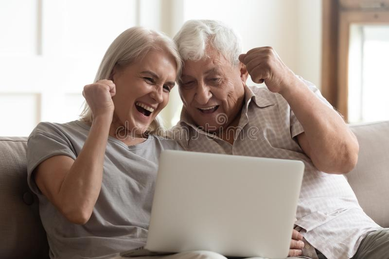 Elderly couple scream with joy celebrating lottery victory lucky moment. Elderly couple seated on couch looking at laptop screen scream with joy feels excited royalty free stock photos