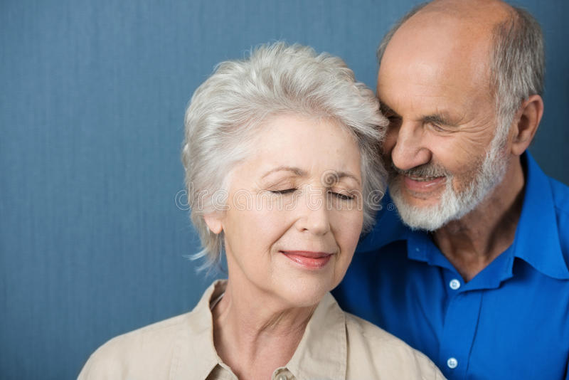 Elderly couple share a tender moment royalty free stock images