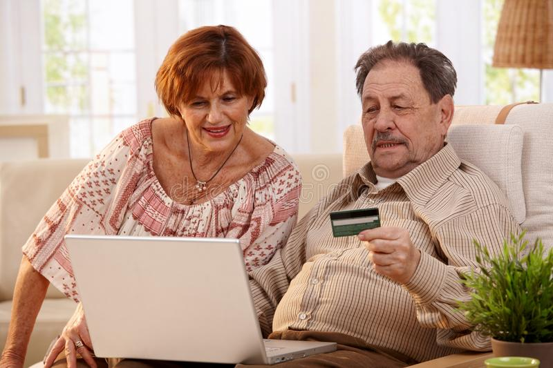 Elderly couple shopping online. At home, using laptop computer and credit card stock images