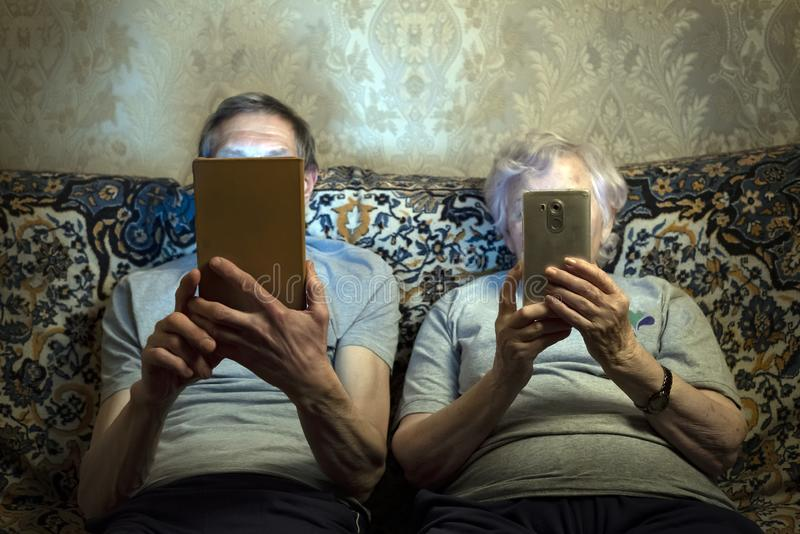 An elderly couple sit on the couch with gadgets, look at them close their faces. stock photo