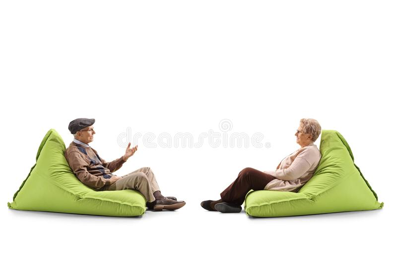 Elderly couple sitting on a bean bag armchairs and talking. Full length profile shot of an elderly couple sitting on a bean bag armchairs and talking isolated on stock photos