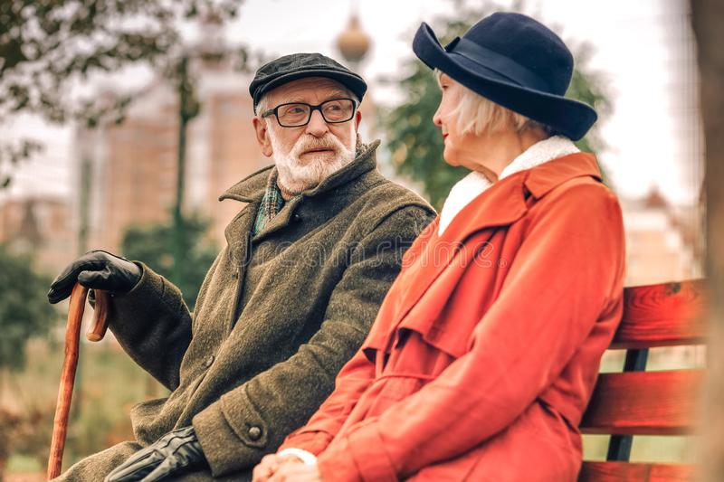 Elderly couple sitting on bench looking at each other royalty free stock image