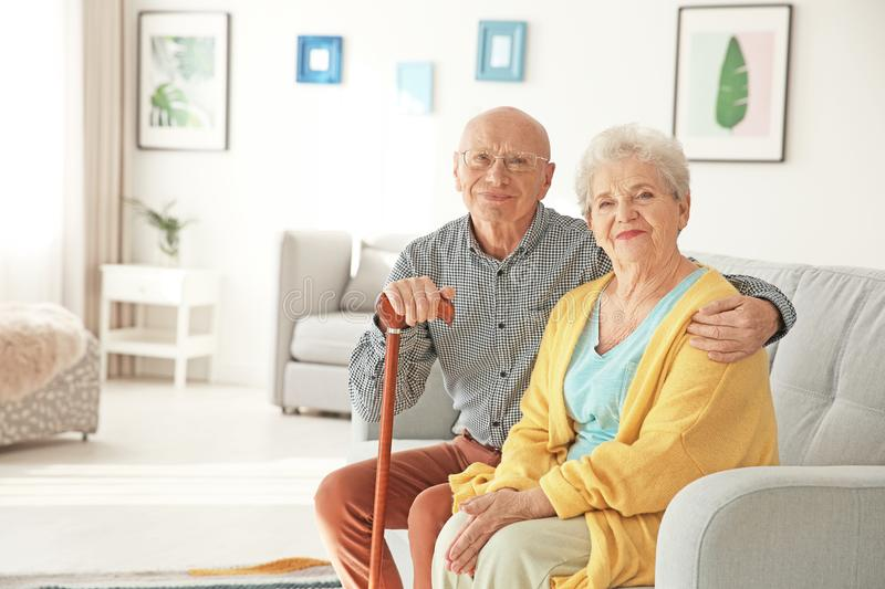 Elderly couple sitting on couch stock image