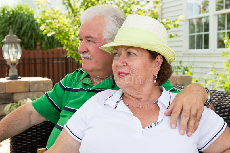Elderly couple sitting gazing into the distance stock photo