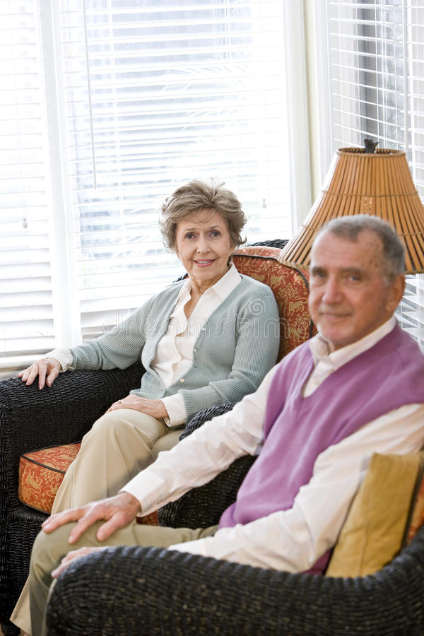Elderly couple sitting on living room couch. Happy elderly couple sitting on living room couch, focus on woman royalty free stock image